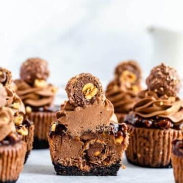 mini nutella cheesecakes stuffed with Ferrero rochers and topped with nutella hazelnut ganache, chocolate whipped cream and chopped hazelnuts