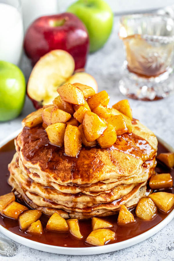 Fluffy cinnamon pancakes with a sweet and gooey apple cinnamon syrup topping. These Apple Cinnamon Pancakes are the perfect breakfast for the fall season! #pancakes #pancakerecipe #breakfastrecipes #breakfastideas #applerecipes