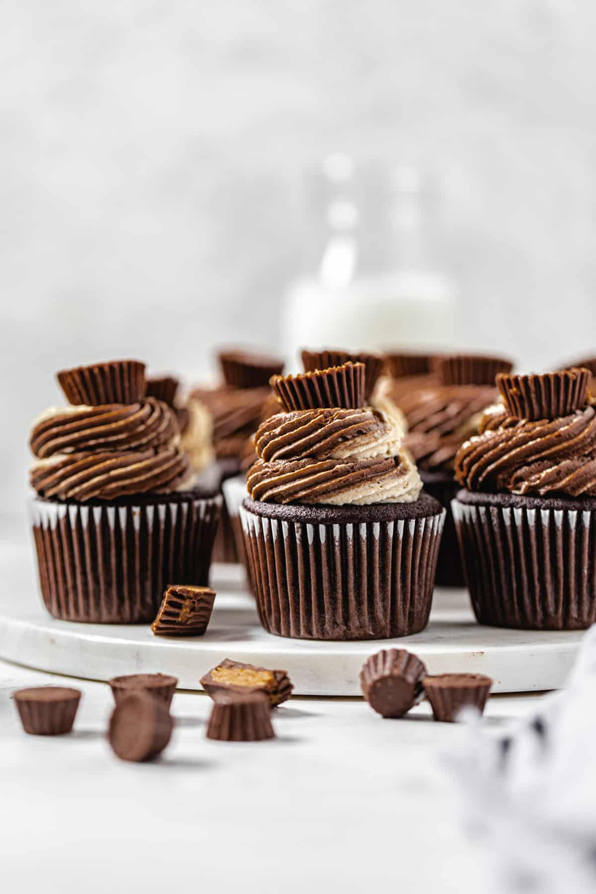 cupcakes on a round marble board with mini Reese's in front and a milk bottle in the background