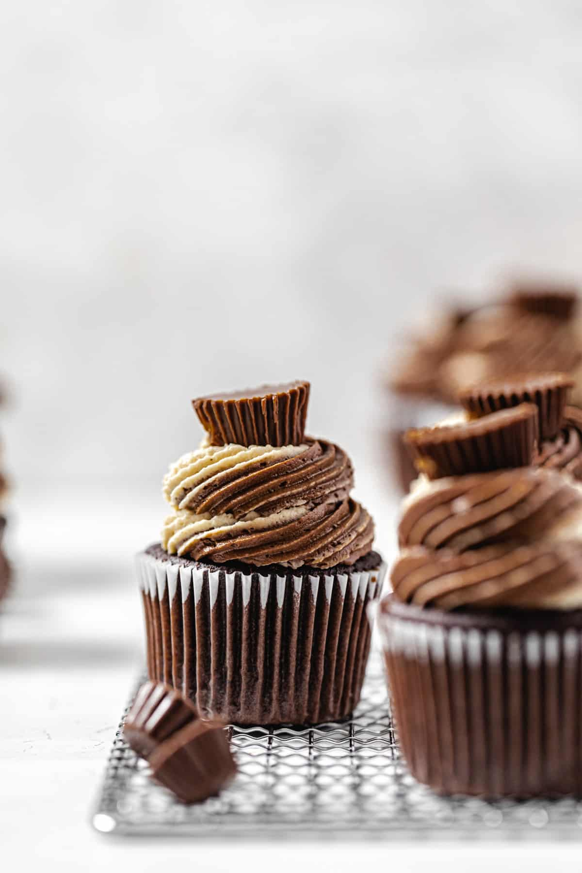 two cupcakes on a small rack with a mini Reese's cup in front of the one in the background