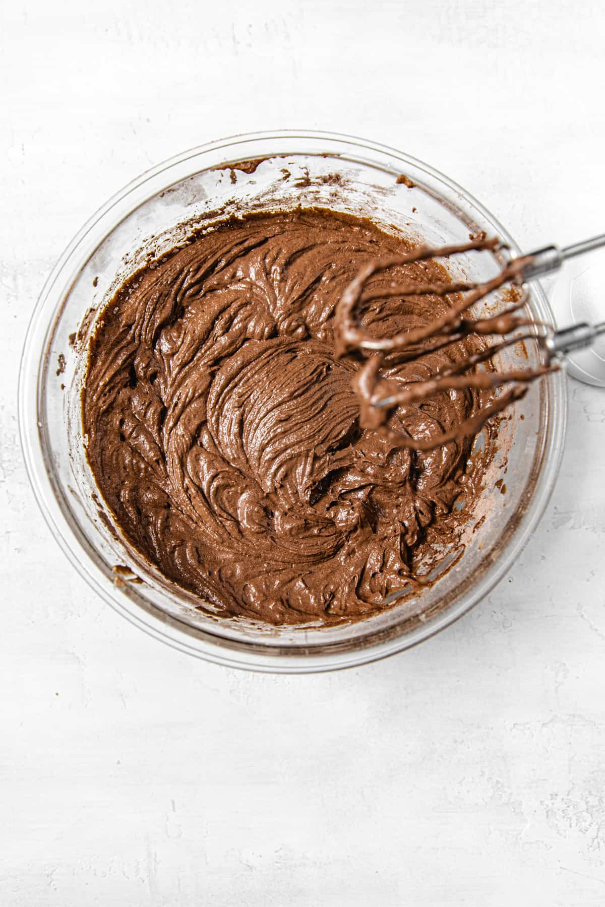 bowl of chocolate cupcake batter with hand mixer over it