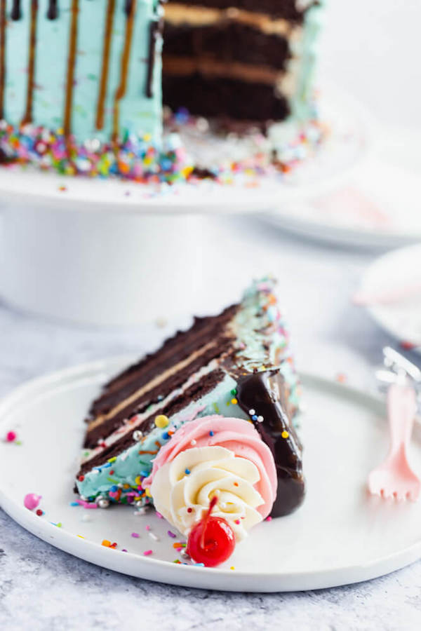 chocolate cake filled with vanilla sprinkle, caramel and chocolate buttercream and covered in a teal sprinkle frosting, topped with maraschino cherries and decorated with more sprinkles.