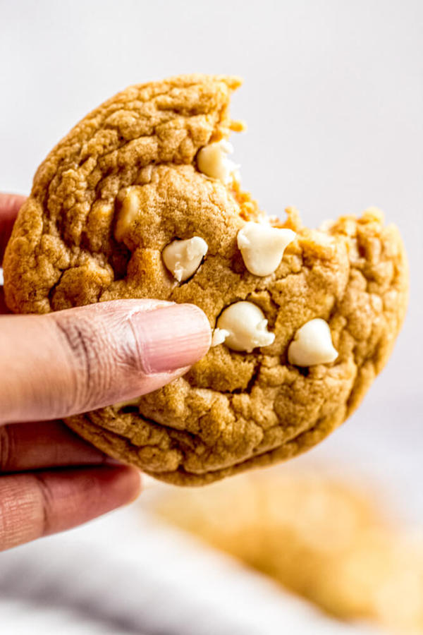 holding up a bite of chocolate chip pumpkin cookie