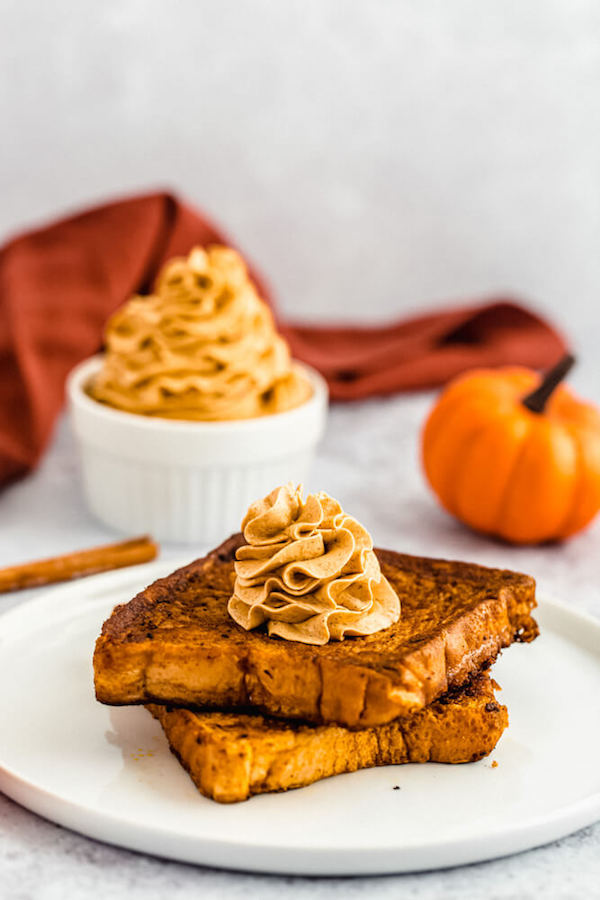 pumpkin French toast topped with icing sugar, maple syrup and whipped pumpkin spice honey butter