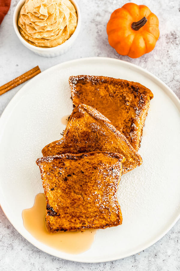 pumpkin French toast topped with icing sugar and maple syrup