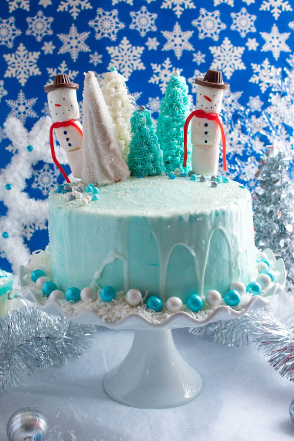 This Winter Wonderland Cake has all the magic and beauty of winter inside a cake! With a wintery white and blue theme, marshmallow snowmen, sugar cone Christmas trees and a powdered sugar snow drip, this is the perfect dessert for your Winter Wonderland themed party!