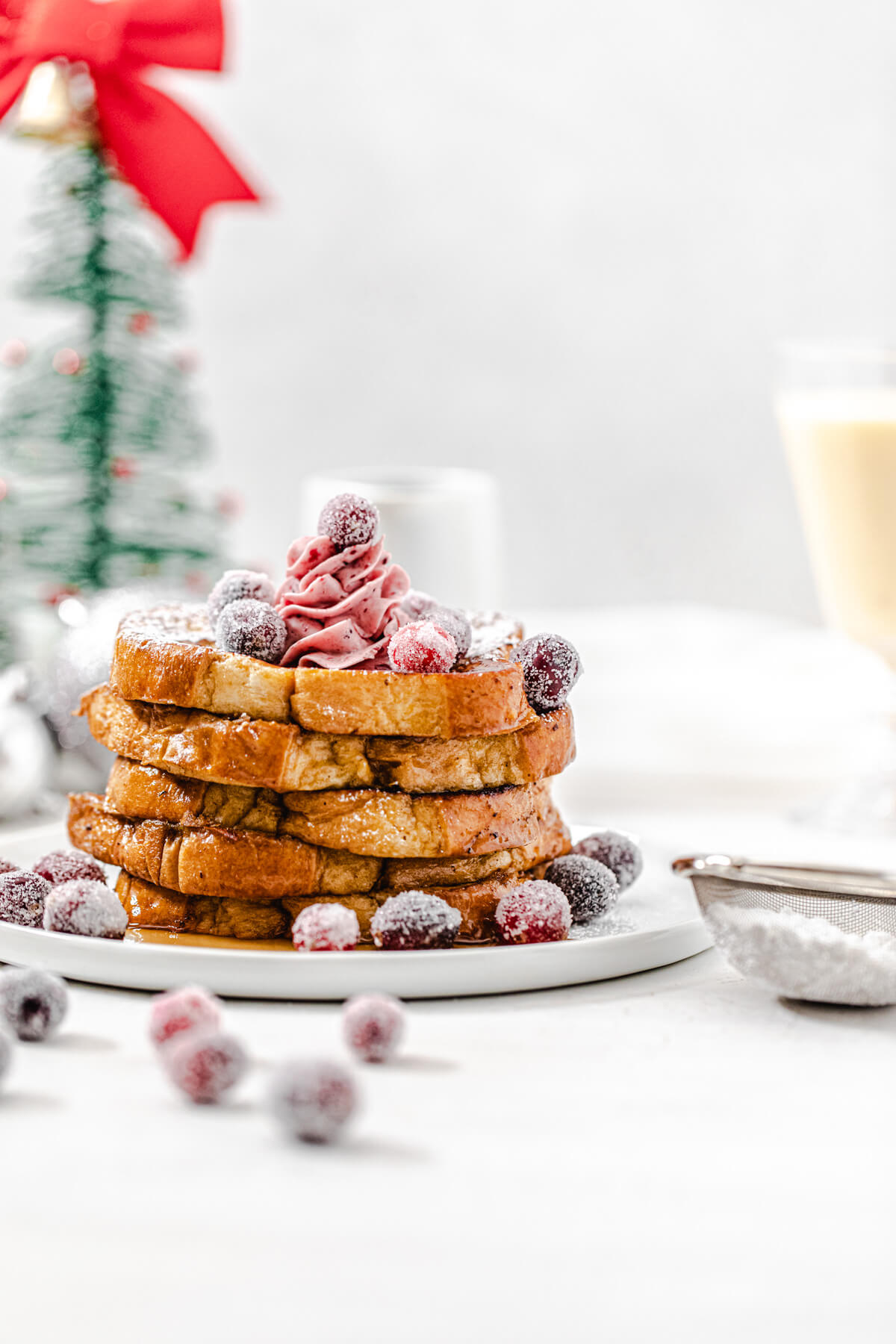 stack of French toast topped with sugared cranberries on a white plate