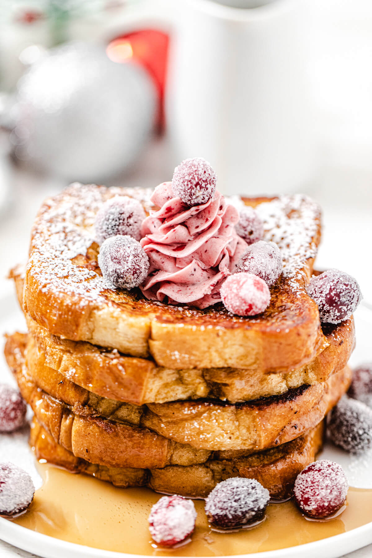 close up of French toast stacked on a white plate topped with sugared cranberries