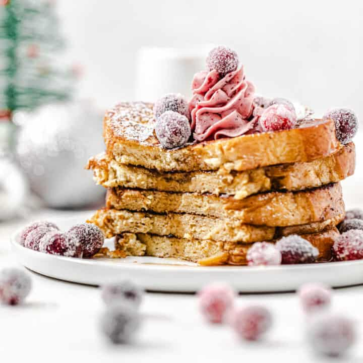 stack of French toast topped with cranberries with the front half sliced off