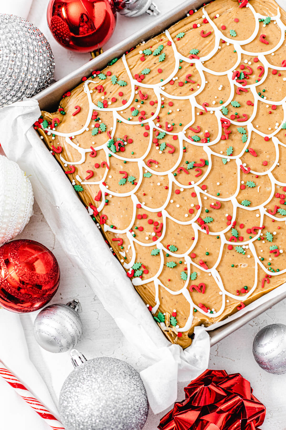 fudge topped with Christmas sprinkles in a square pan with red and silver ornaments around the side of the pan