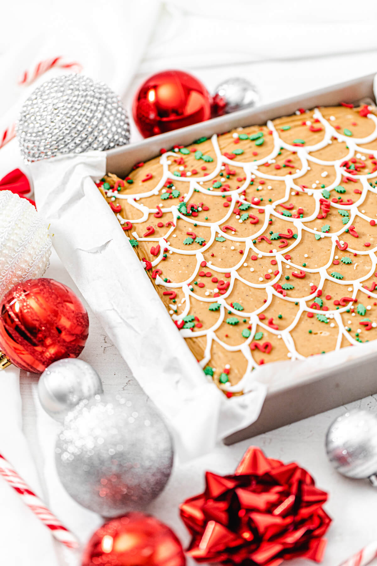 gingerbread fudge in a square pan with red and silver ornaments surrounding it