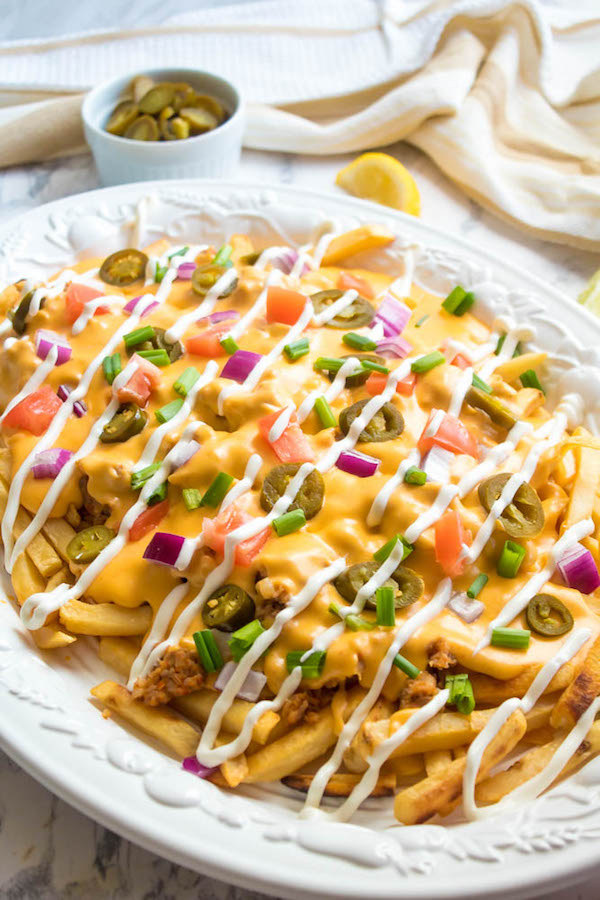 These Loaded Cheese Fries are guaranteed to be a crowd pleaser! Crisp french fries loaded with hot Italian sausage, jalapeños, red onions, green onions, tomatoes, sour cream and a creamy and delicious cheese sauce!