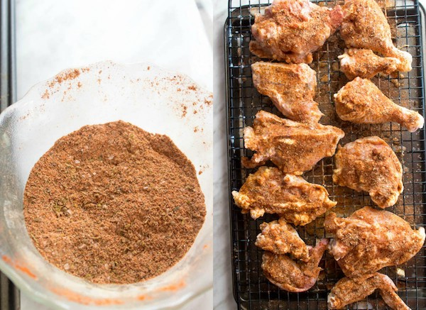 seasoning in a small bowl and seasoning on raw chicken pieces on a cooling rack and baking sheet
