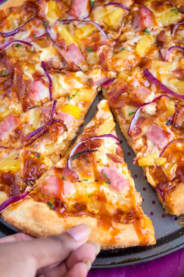 Hawaiian BBQ Pizza — Thick and chewy pizza crust topped with tangy barbecue sauce, ham, pineapple, bacon, red onions and loads of cheese. This flavourful pizza will definitely be your family's new Friday night fave!