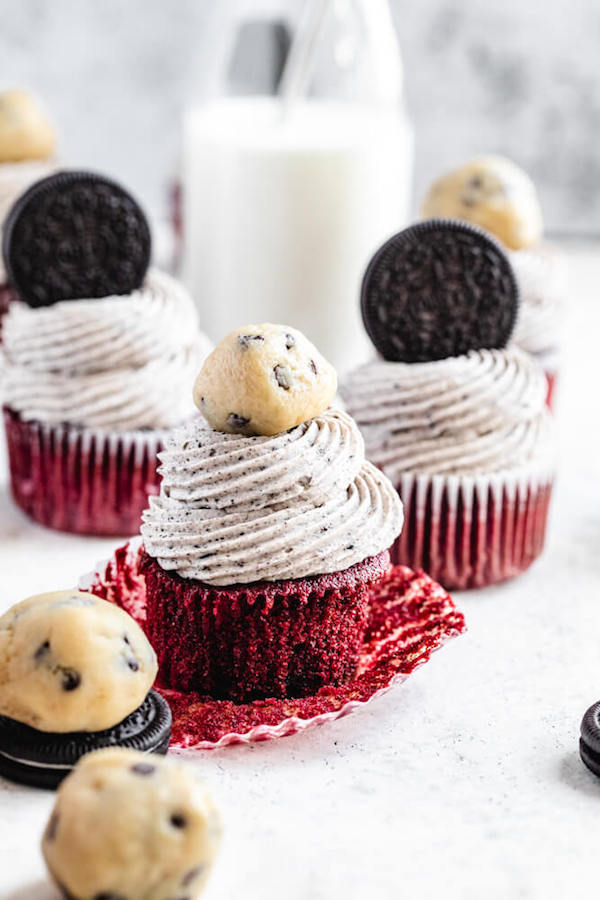 unwrapped red velvet cupcake topped with cookies and cream frosting and a cookie dough ball