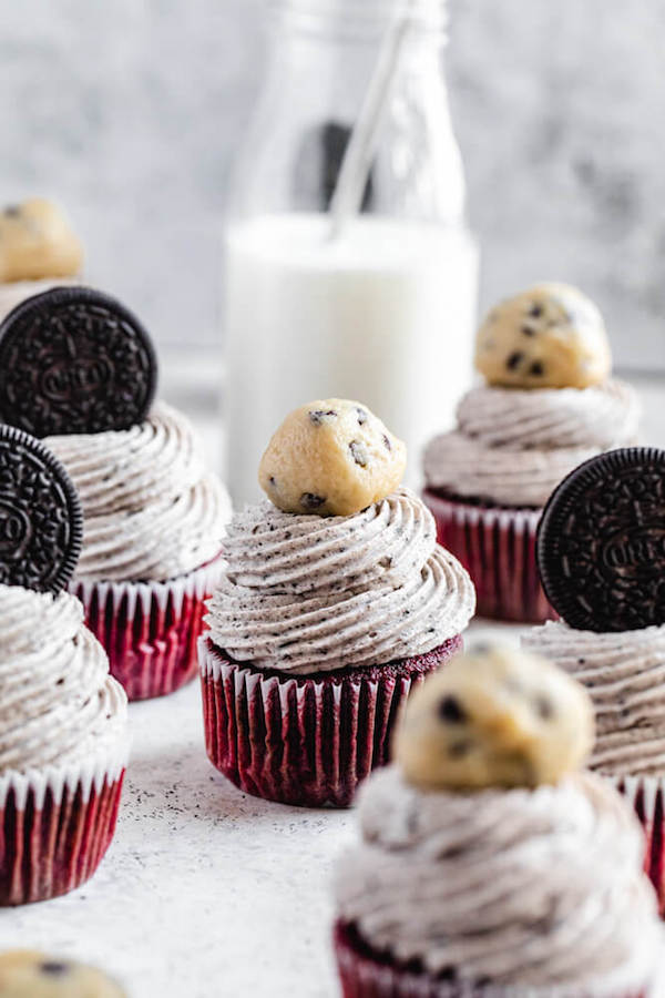 red velvet oreo and cookie dough cupcakes with milk bottle in the background