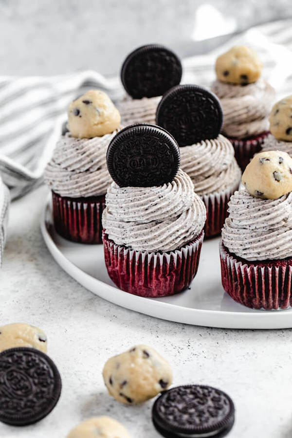 cupcakes topped with Oreos and cookie dough balls on a white plate