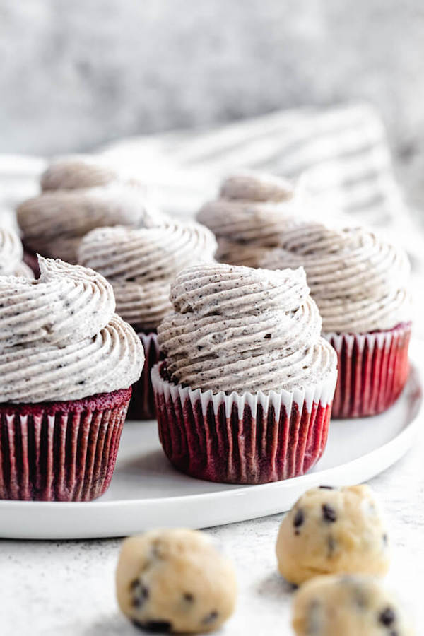 red velvet flavoured cupcakes topped with cookies and cream cheese frosting on a white plate
