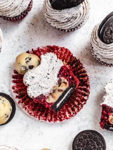 red velvet cupcake cut in half showing Oreo cookie and cookie dough ball inside
