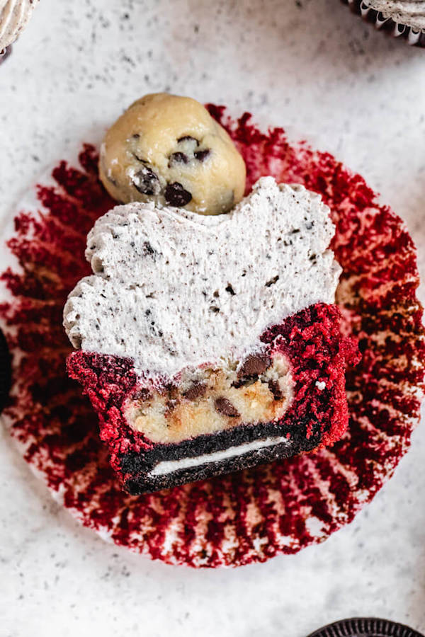 halved red velvet cupcake stuffed with Oreo and cookie dough