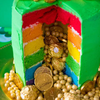 This Pot of Gold Rainbow Cake is the perfect dessert for St. Patrick's Day! Six colourful rainbow cake layers, filled and decorated with the most precious gold goodies!