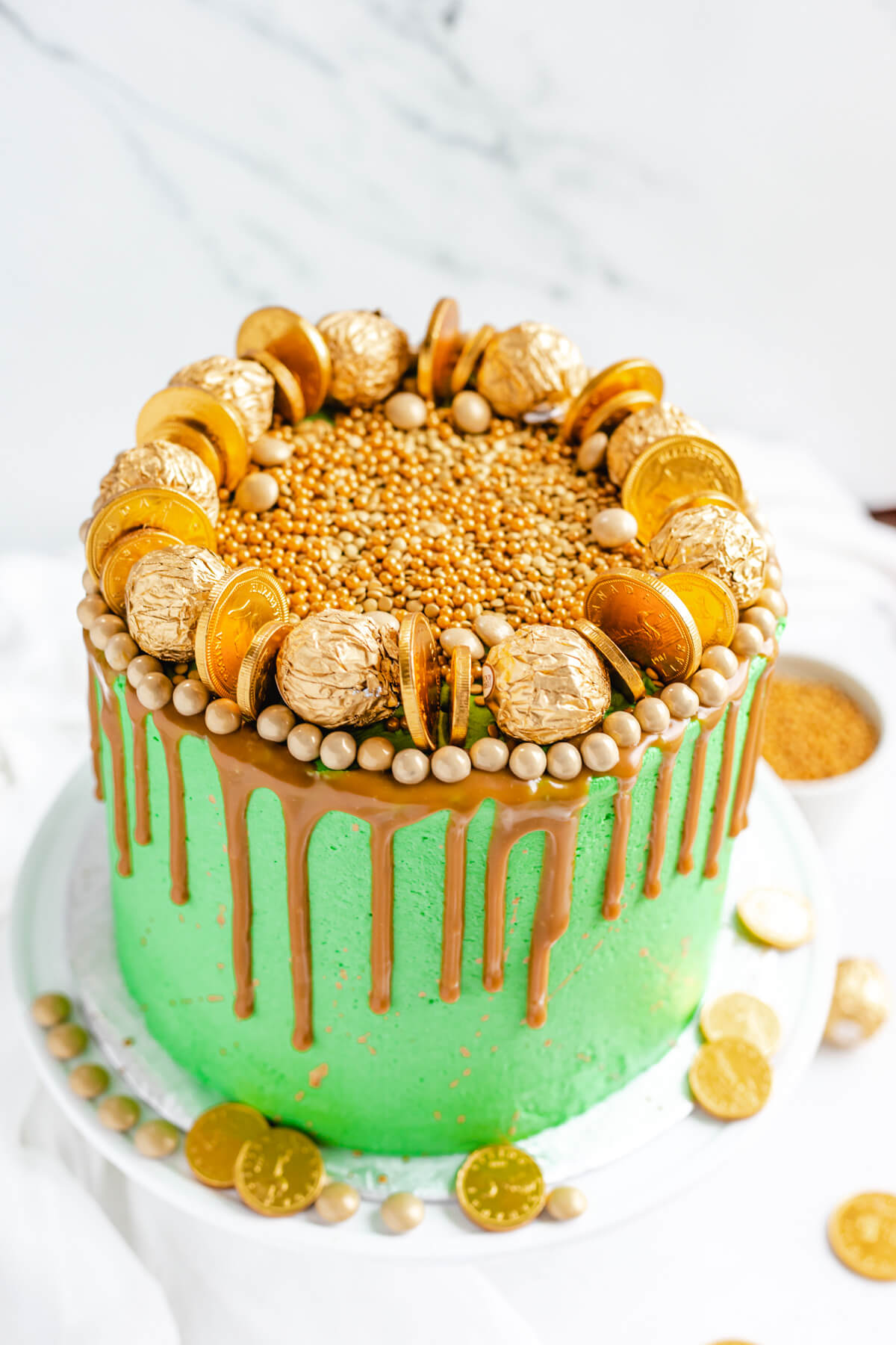 cake covered in gold candies on a white cake stand