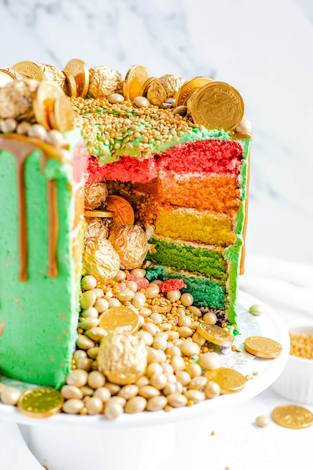 gold candies coming out of rainbow cake