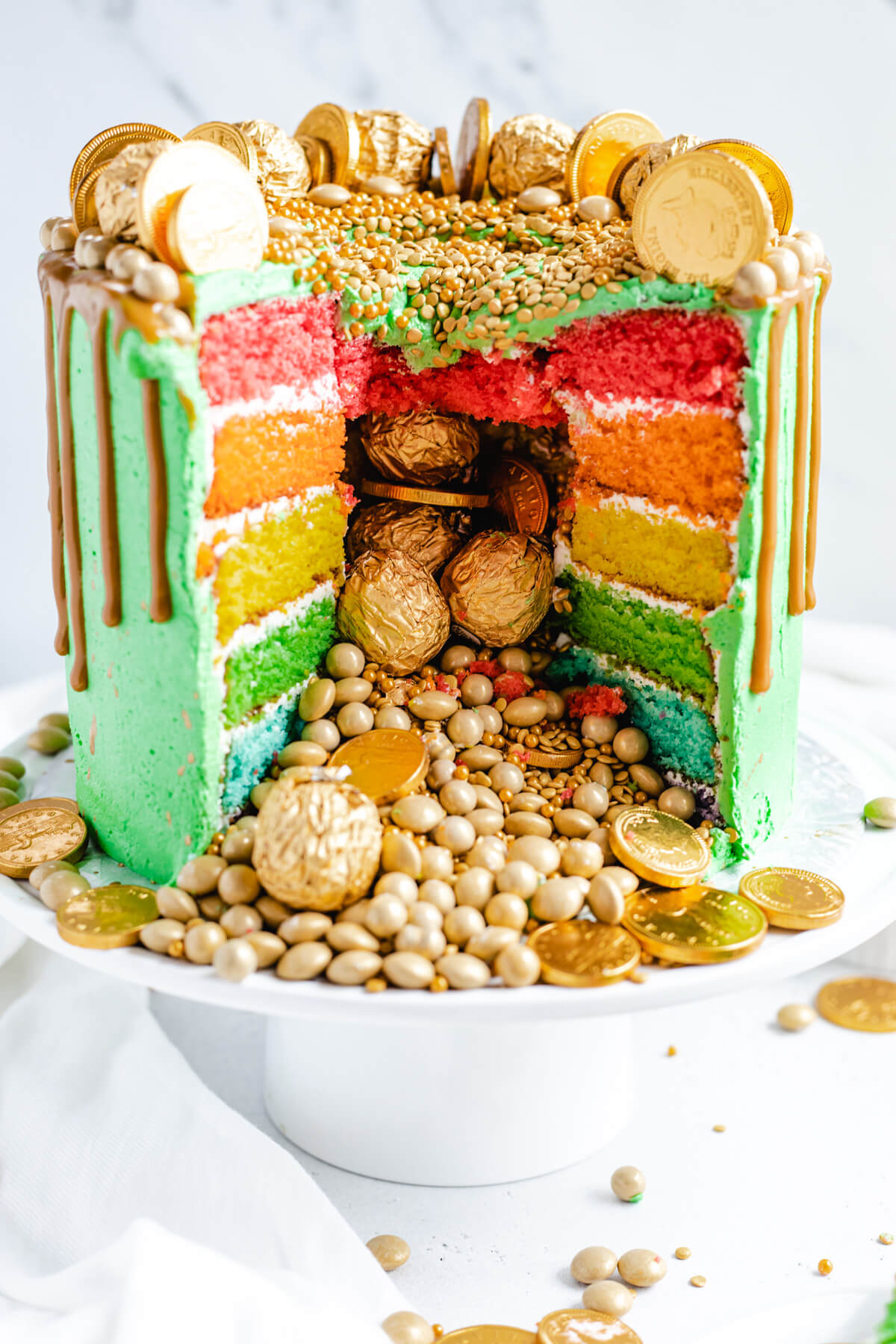 gold candies and sprinkles spilling out of a cake