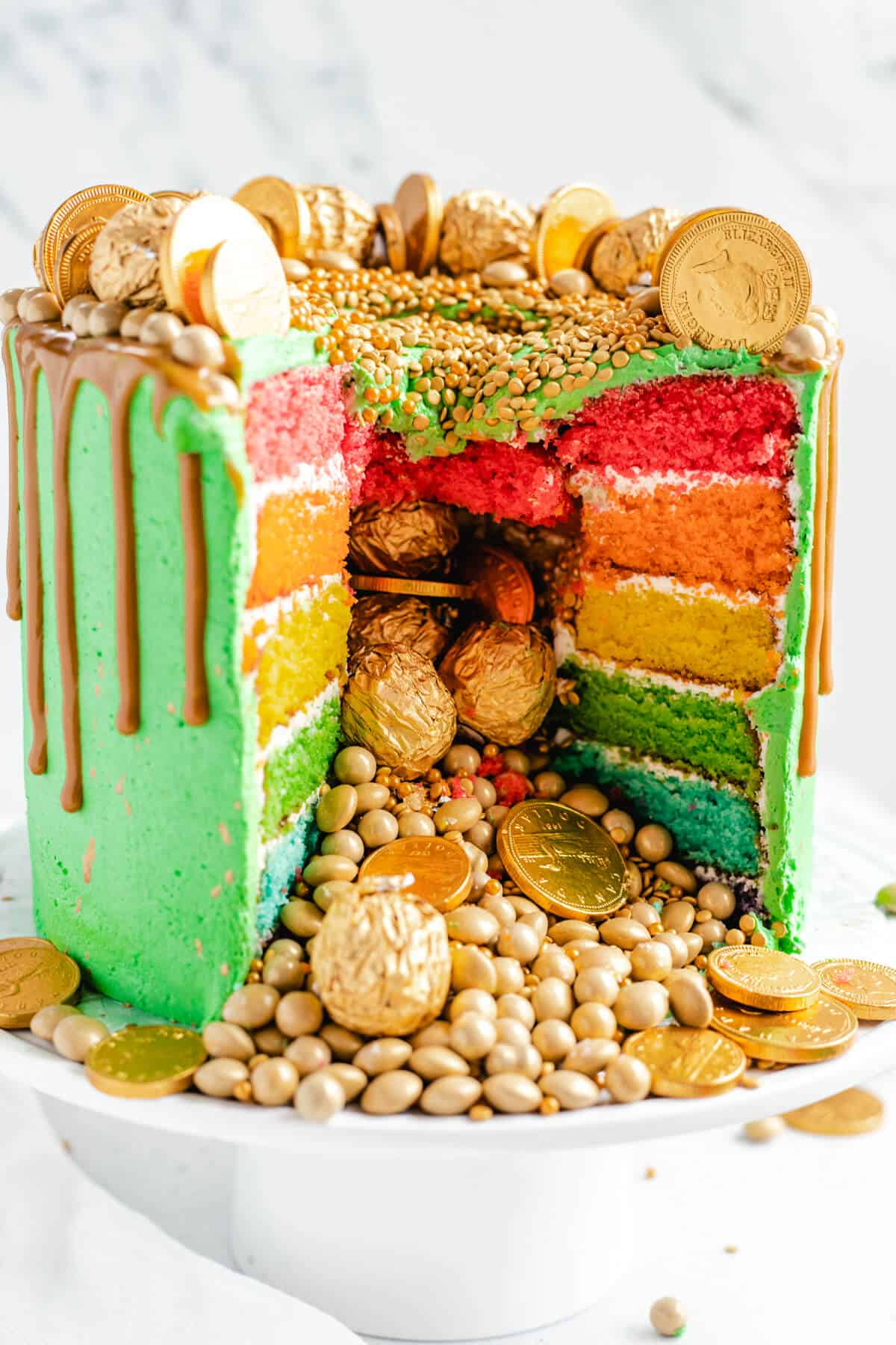 rainbow piñata cake with gold candies falling out