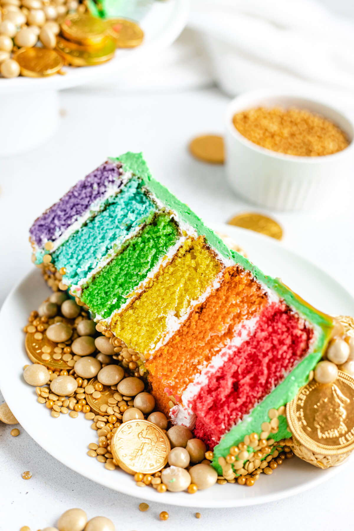 rainbow cake slice with gold sprinkles on a white plate