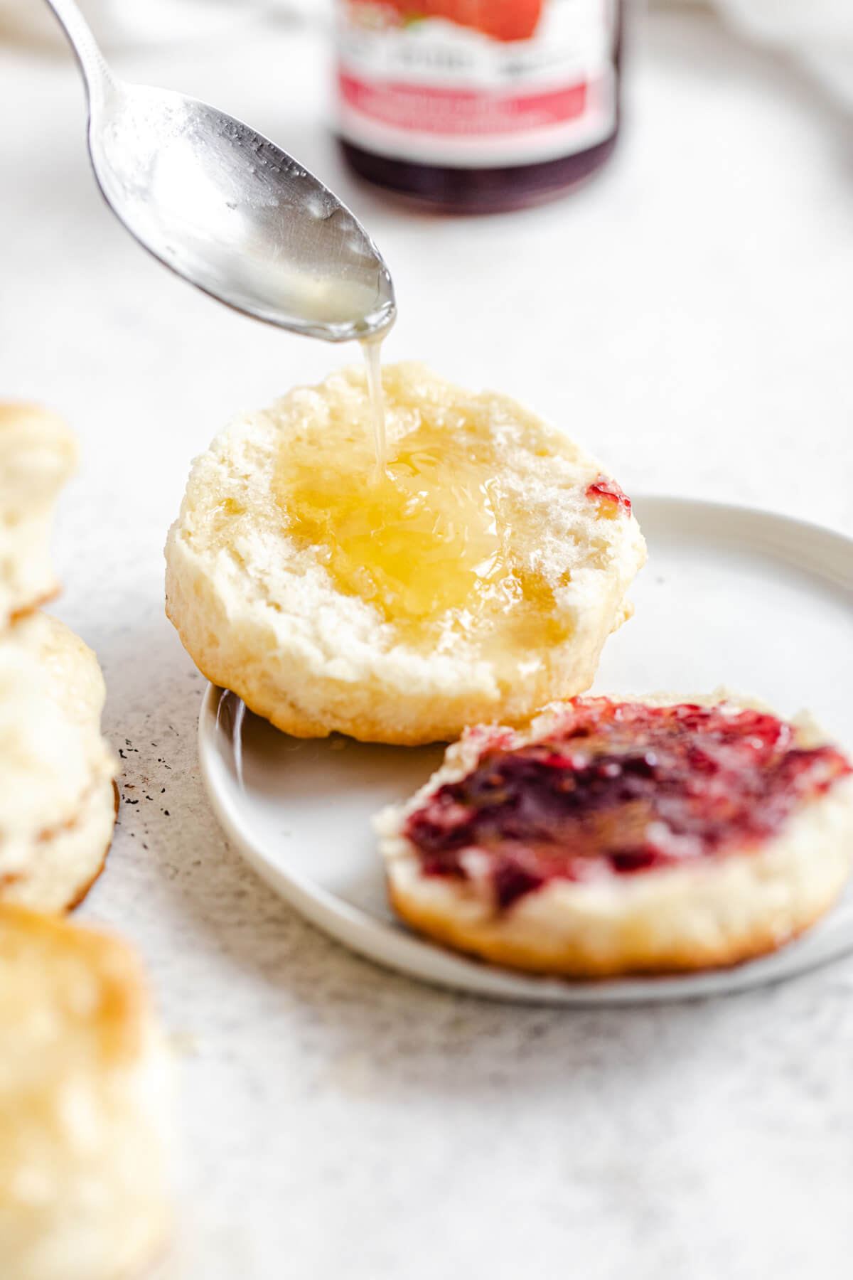 pouring honey butter on one side of a biscuit with jam on the other half