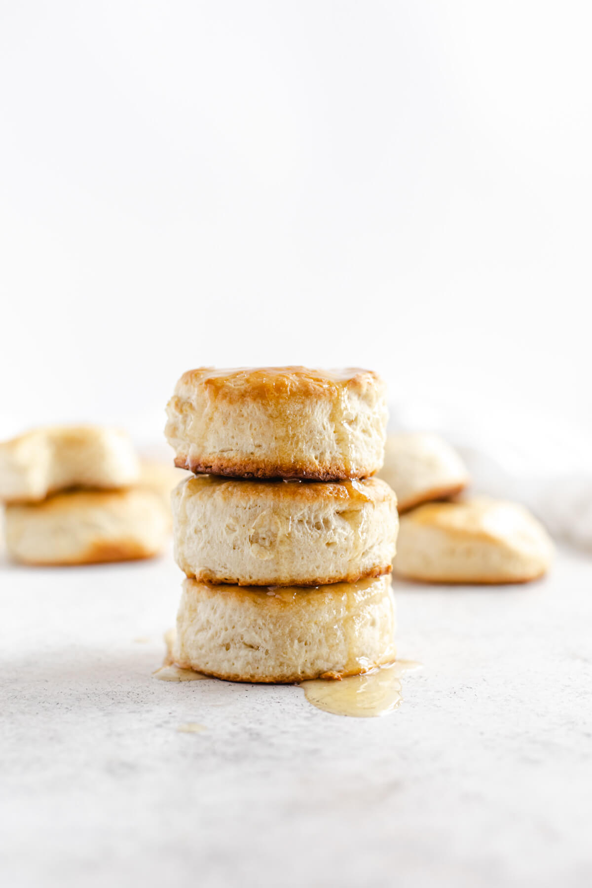 three biscuits stacked on top of each other with honey butter dripping down