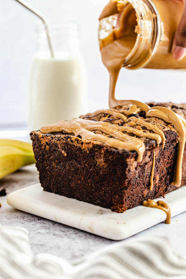pouring melted peanut butter onto chocolate flavoured banana bread loaf