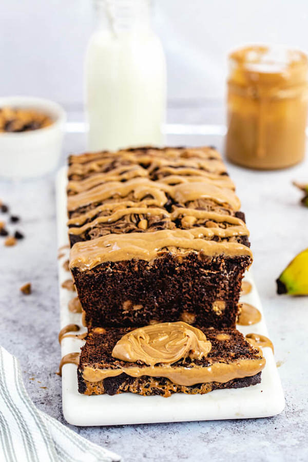 sliced chocolate banana bread loaf with a dollop of peanut butter in the middle of a slice