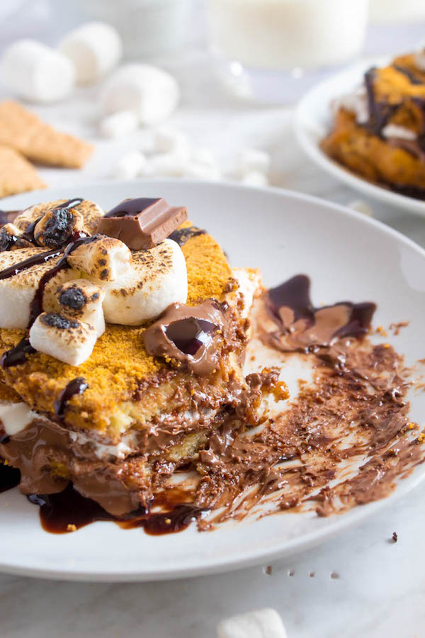 This S'mores French Toast is the ultimate summer breakfast! Graham cracker french toast filled and topped with toasted marshmallows, rich chocolate bars and chocolate sauce. Totally diet-friendly (yeah right) and super easy to make!