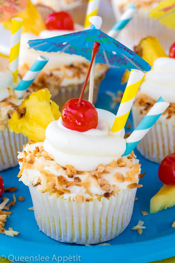 These Pina Colada Cupcakes are a yummy tropical treat perfect for the summertime! It starts with a moist Pina Colada flavoured cupcake, then it's filled with a pineapple sauce, frosted with a Pina Colada buttercream, dipped in toasted coconut and decorated with cherries, pineapples, umbrellas and cute little straws to resemble a Pina Colada!