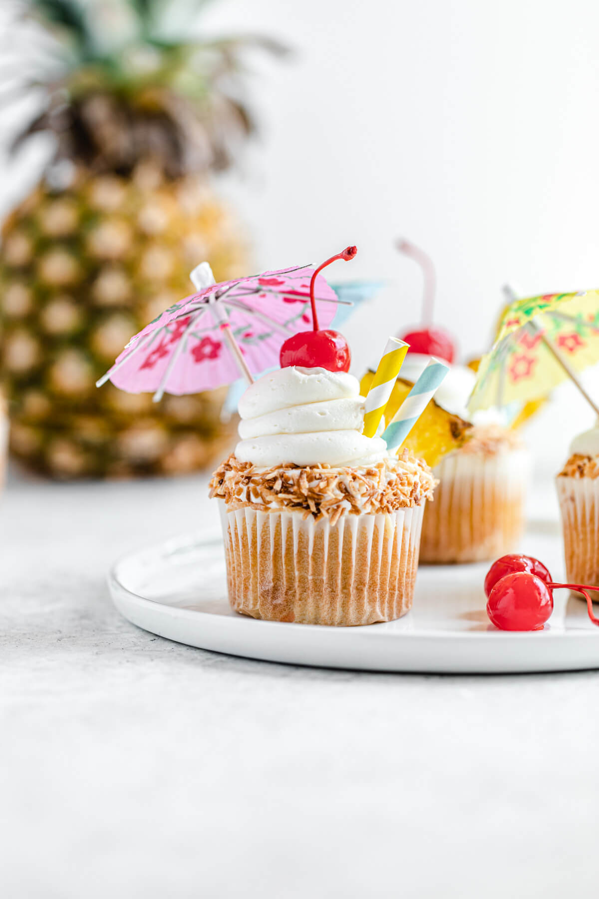 cupcake topped with umbrellas on a white plate with pineapple behind them