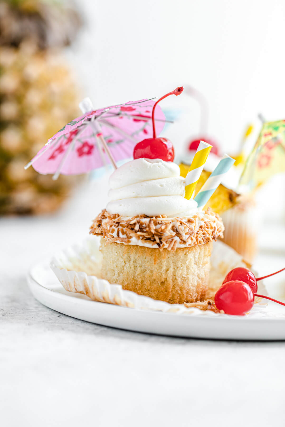 unwrapped cupcake on a white plate with pineapple in the background