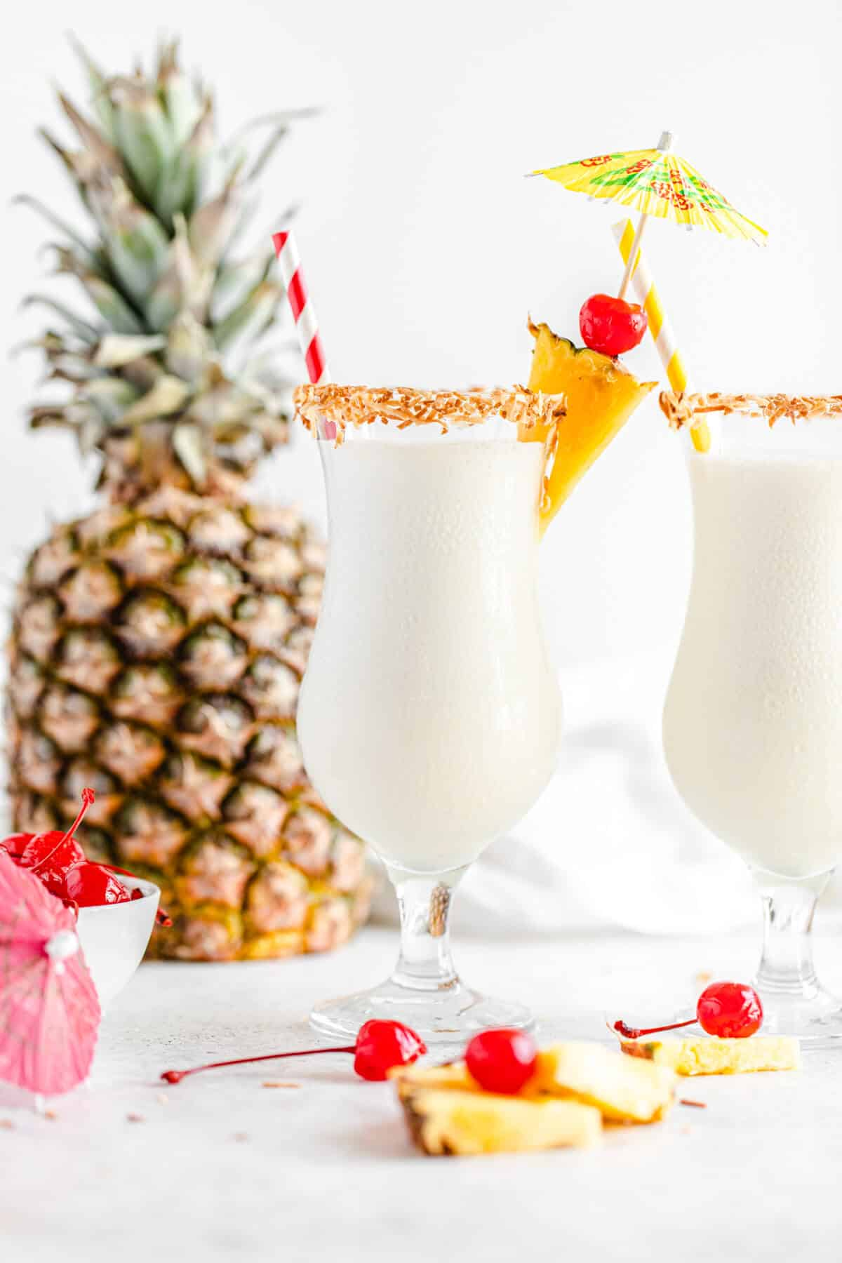 two glasses of milkshake with a pineapple in the background