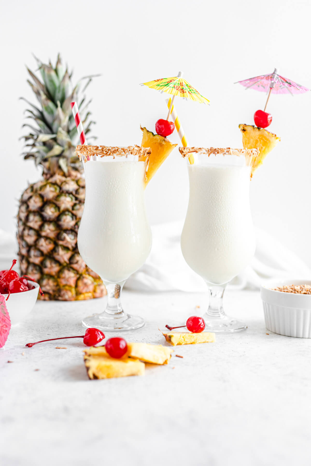 two glasses of milkshake with cherries, toasted coconut and pineapple around