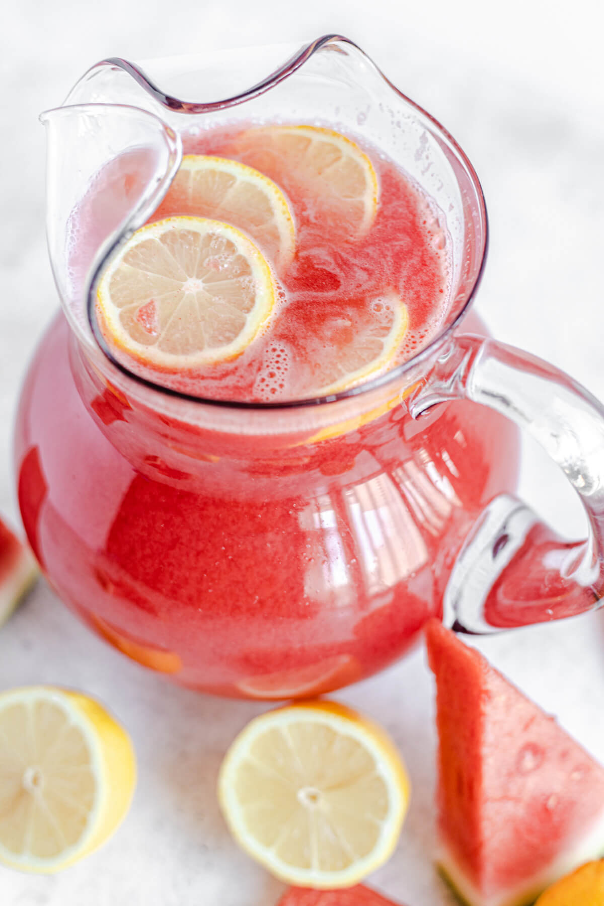 watermelon lemonade in a glass pitcher with lemon slices inside