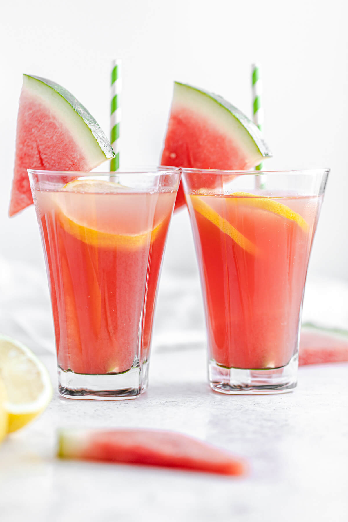 two glasses of lemonade garnished with watermelon wedges and green paper straws