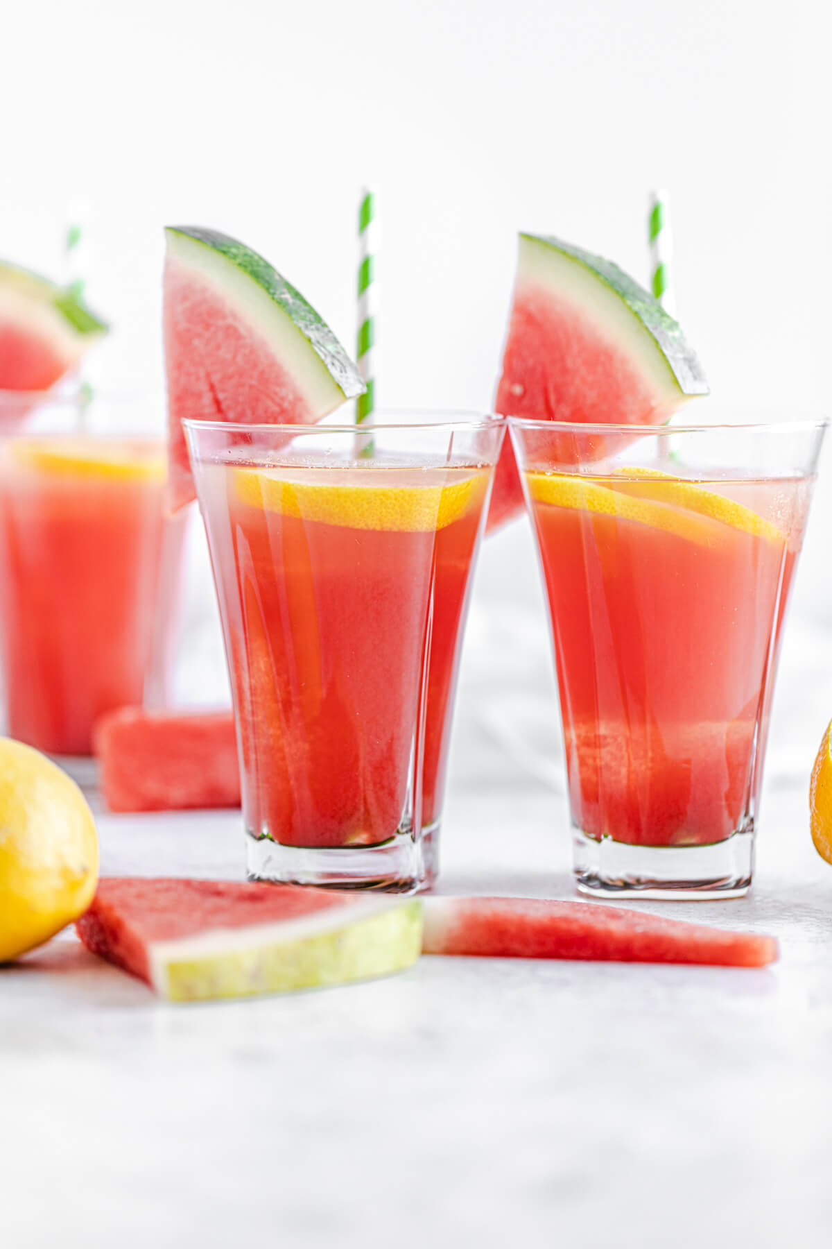 two glasses of watermelon flavoured lemonade with lemons and watermelon in front of them