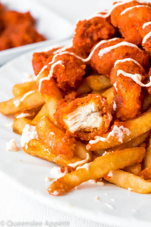 Buffalo Chicken Fries — Crispy fries are loaded with even crispier bite-sized chicken pieces coated in a spicy buffalo sauce and drizzled with a spicy aioli. These quick, easy and delicious Buffalo Chicken Fries are sure to be a crowd pleaser!
