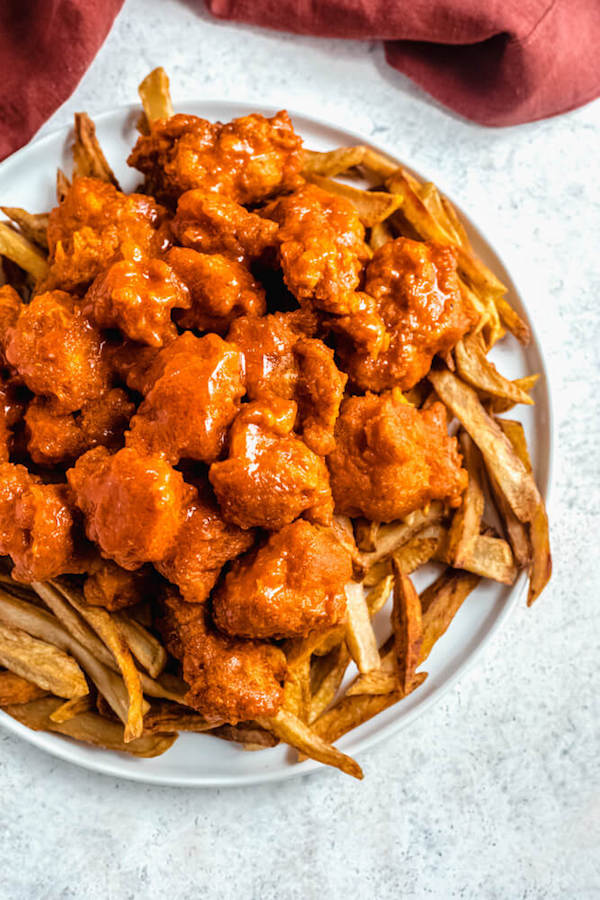 boneless buffalo chicken bites on top of crispy fries