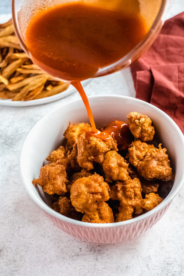 pouring buffalo hot sauce over fried chicken pieces in a bowl
