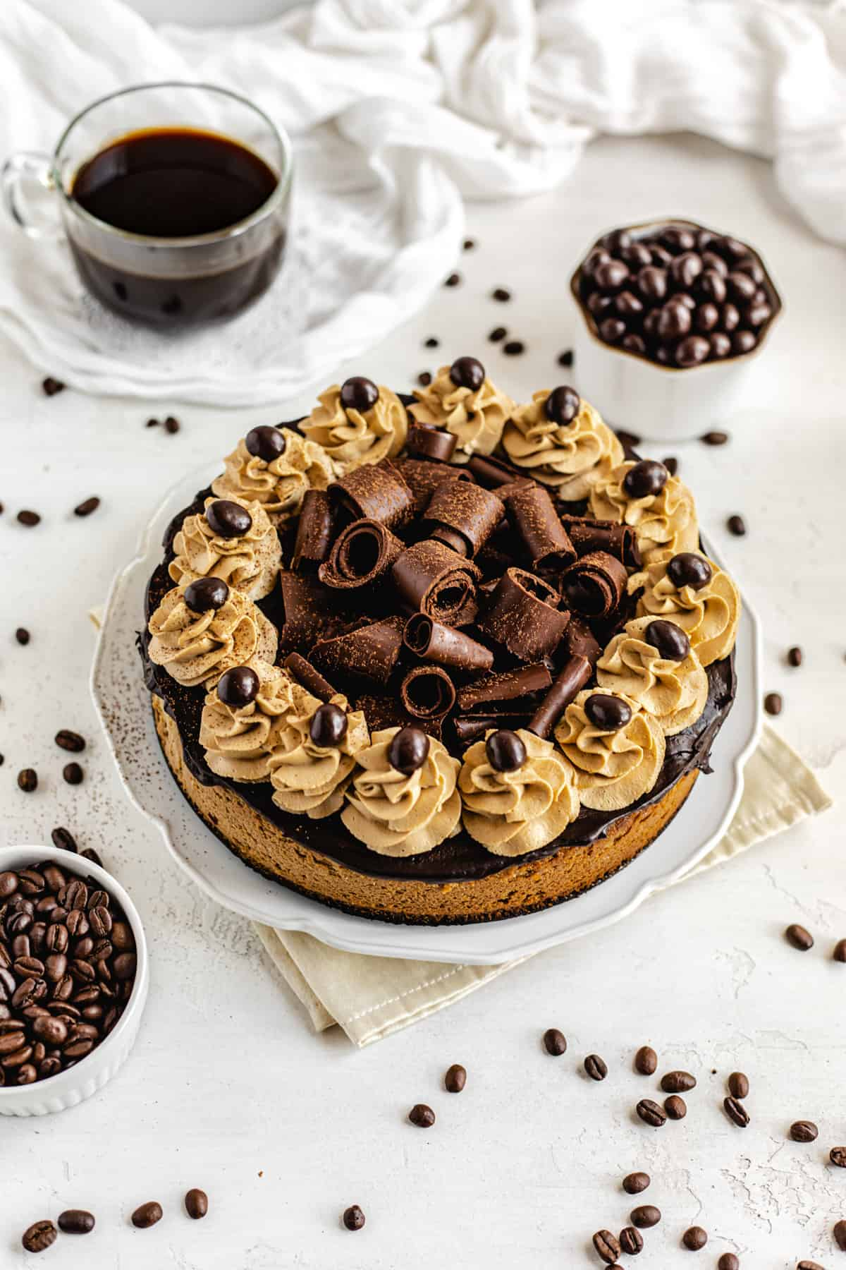 cheesecake on a white platter surrounded by coffee and coffee beans