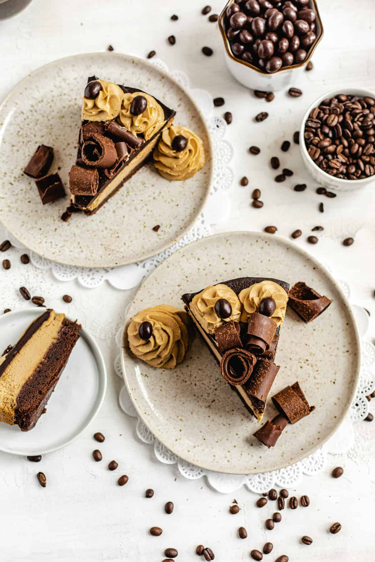 three slices of cheesecake on three plates with coffee beans around them