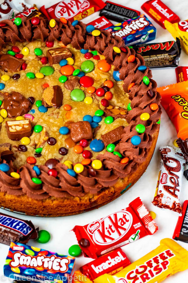 Got leftover Halloween Candy? Use it to make cookies. Or better yet, a giant cookie! This Leftover Halloween Candy Cookie Cake is soft, chewy and loaded with yummy assorted chocolate bars and sweets!