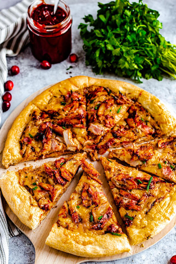 slices of cranberry bbq turkey pizza on a pizza stone